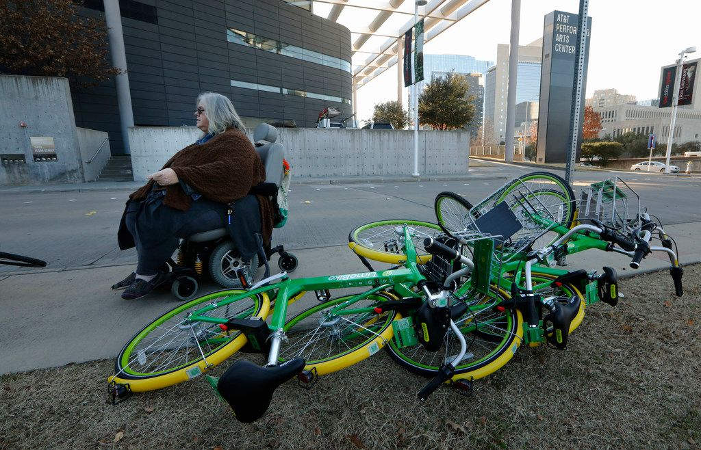 Melody Townsel, who teaches AP English at Booker T. Washington High School for the Performing and Visual Arts, maneuvers her wheelchair past knocked-over rental bikes near the school in Dallas on Monday, January 8, 2018. She uses public railway transit to get to work and often finds bikes and their riders to be problematic.