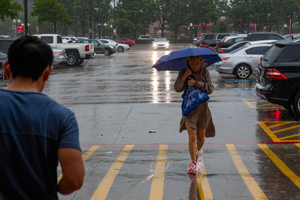 Lauren Wottlin, 32, from Dallas runs through a downpour to enter the Target store at Cityplace Market during a severe thunderstorm in Dallas on Sunday, June 16, 2016. Wottlin wore plastic bags over her designer shoes to keep them dry, she said. (Lynda M. Gonzalez/The Dallas Morning News)