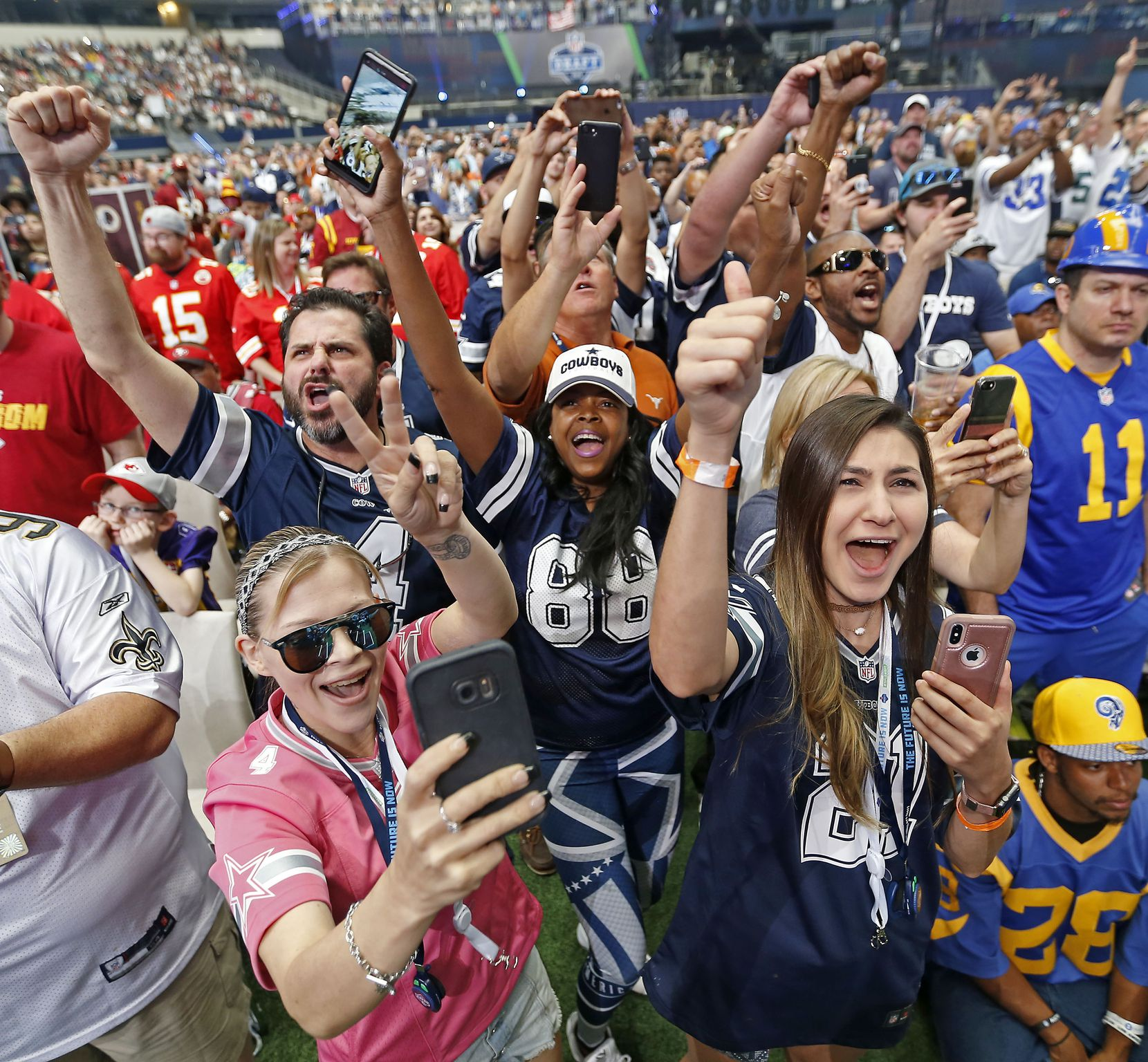 Dallas Cowboys fans including Lisa Morton, who wears a #88 jersey, cheered when the Cowboys selected Dorance Armstrong in Round 4 of the 2018 NFL Draft at AT&T Stadium in Arlington, Texas, in April 2018. The draft filled Dallas hotel rooms more than any other event this year.