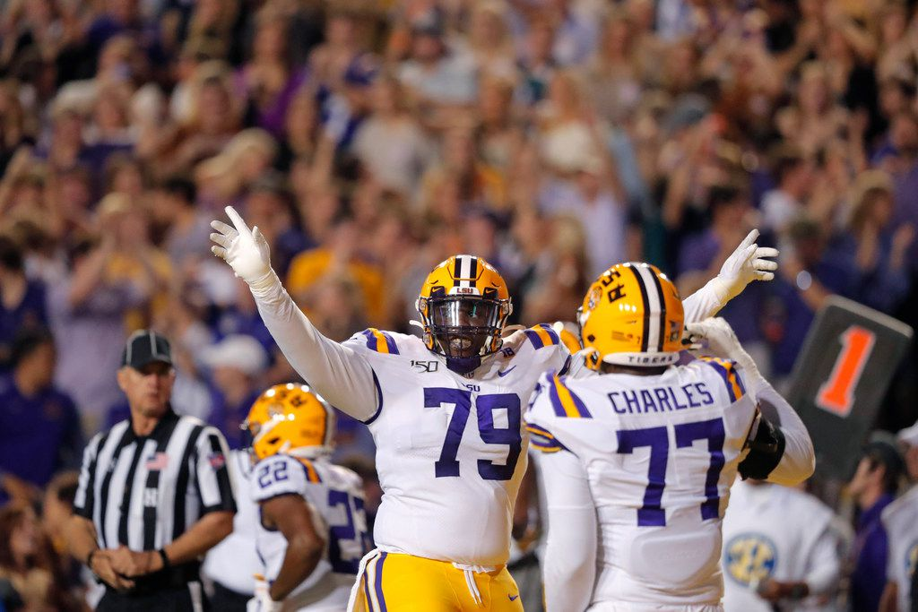 LSU center Lloyd Cushenberry III (79) and offensive tackle Saahdiq Charles (77) celebrate a touchdown in the first half of an NCAA college football game against Texas A&M in Baton Rouge, La., Saturday, Nov. 30, 2019. (AP Photo/Gerald Herbert)