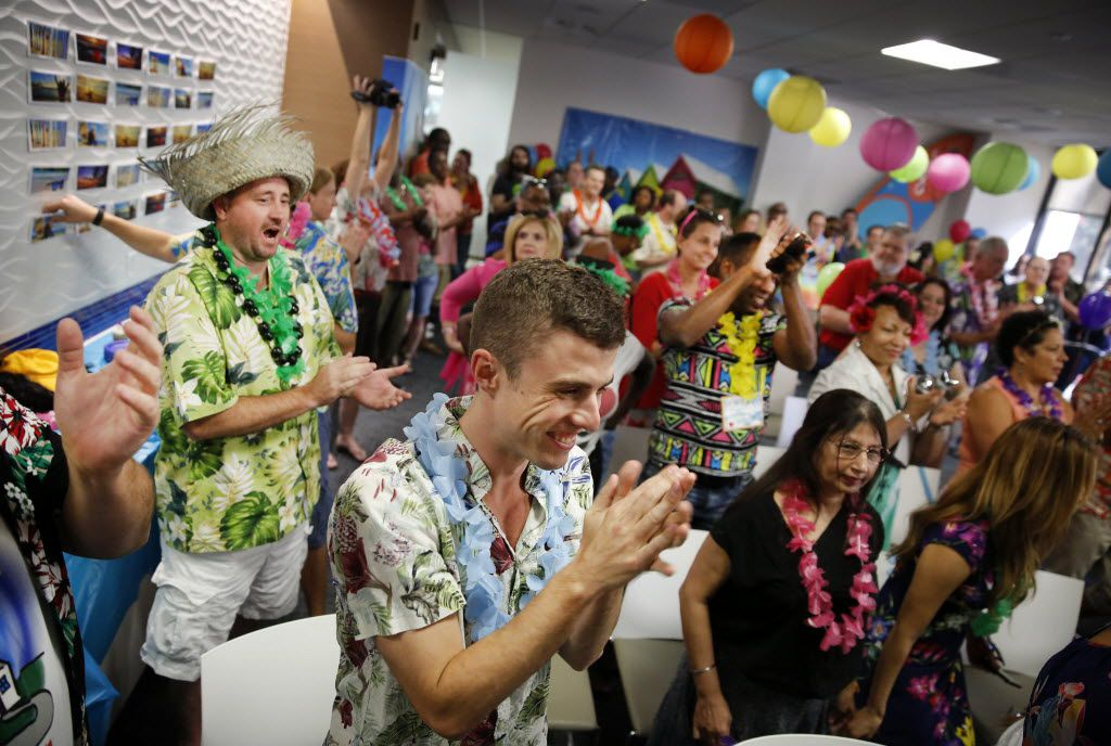Alex Morin (center) and his co-workers applaud Heidi Fessler  (not pictured) for her award at a Santa Barbara Beach Party.