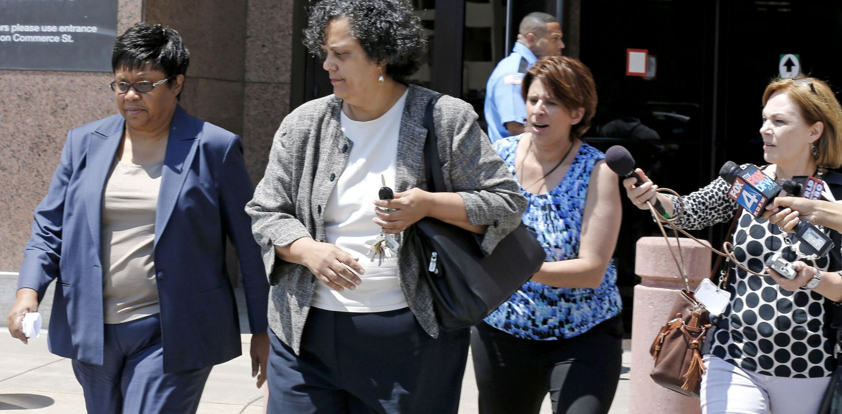 """Kathy Nealy (left) and her attorney Cheryl Wattley leave the Earle Cabell Federal Building in July 2014. Nealy was indicted and accused of secretly funneling almost $200,000 to Dallas County Commissioner John Wiley Price as a """"straw purchaser of four pieces of real estate, and handing over more than $100,000 in rent payments from a property."""