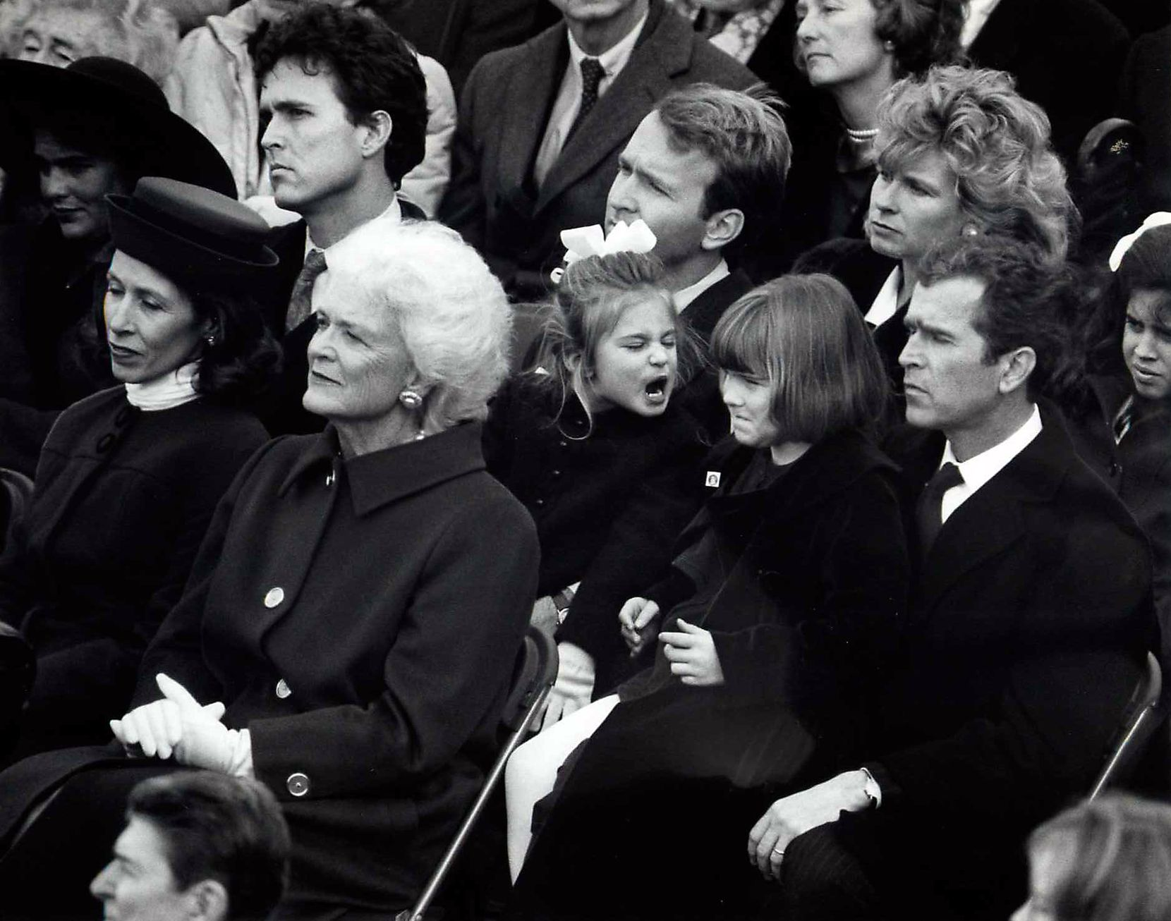Barbara Bush watches as her husband George H.W. Bush is inaugurated president of the United States on Jan. 20, 1989. Behind her, George W. Bush holds his daughter Jenna, 7,  on his lap as she and her cousin Lauren Bush, 4, (on the lap of her father, Neil) have a disagreement.