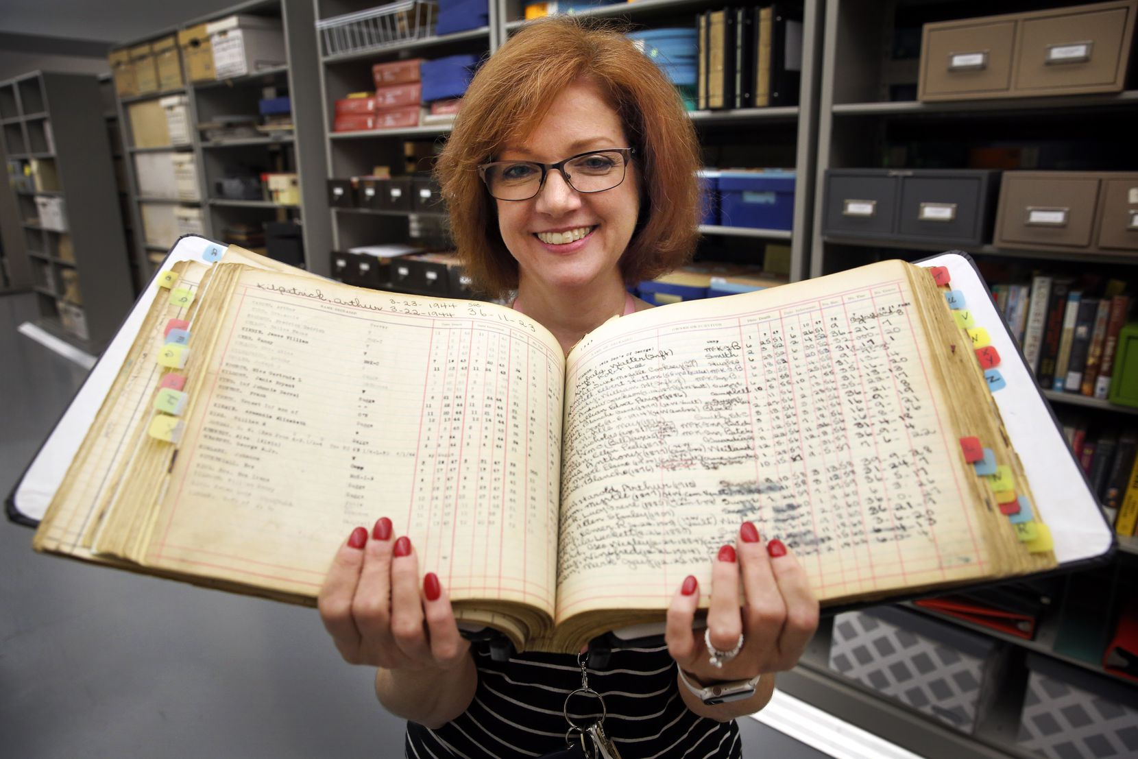 Christine Sharbrough, manager of the downtown library's Dallas History & Archives Division, is now tasked with cleaning and organizing the Oakland Cemetery archives. Here she holds one the burial ledger.