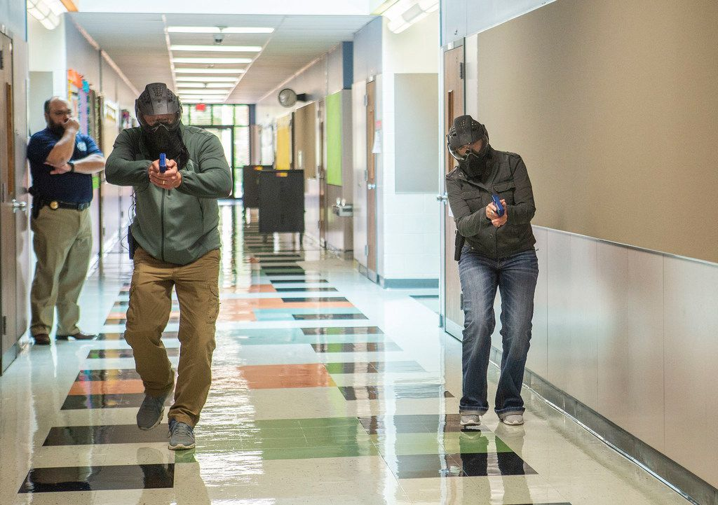 Michael Antu, the Director of Enforcement and Special Services at the Texas Commission on Law Enforcement, supervises as two school employees training to become armed school marshals run through a practice drill at Windermere Elementary School in Pflugerville, Texas on August 10, 2018.