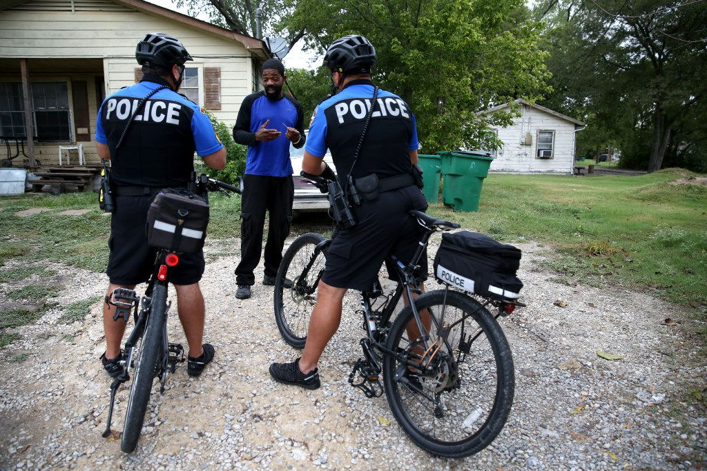 McKinney neighborhood police officers Sgt. Damian Guerrero (left) and Randy Patton talk to Darron, who flagged the pair down to ask a question, while they patrol east of downtown McKinney, Texas on Sept. 26, 2016. (Rose Baca/The Dallas Morning News)