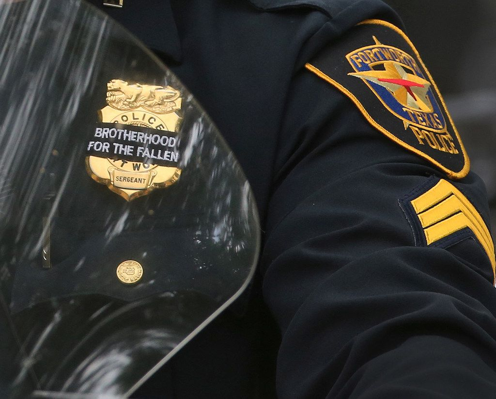 Law enforcement officers wear ribbons over their badges at the funeral for Dallas Officer Rogelio Santander.