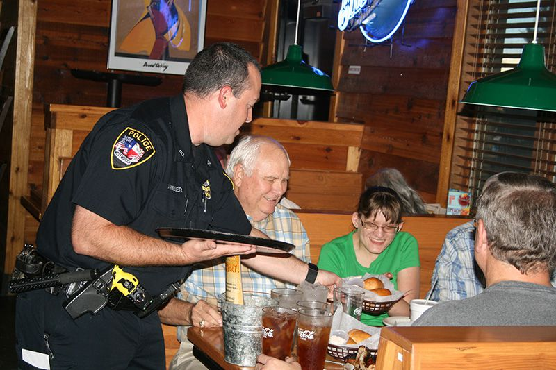 Westworth Village Police Officer Jeramy Miller serves hot rolls to the Crump family of Fort Worth as part of his job during Tip A Cop at Texas Roadhouse on Hulen in Fort Worth. During the tasty fundraiser, Law Enforcement Torch Run (LETR)members like Miller worked the dinner shift for tips to later donate to Special Olympics Texas. Miller participated in the torch run at the national Special Olympics games in New Jersey in 2014. Shelby Crump, third from the left, has been an athlete for Special Olympics for a number of years. Also pictured is her grandfather, Glen Crump./Photo by Di Hall
