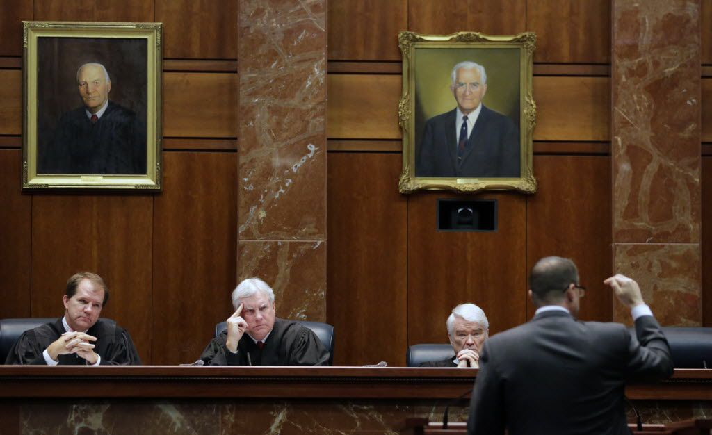 Justice Don Willett (left), shown in a 2015 oral argument at the Texas Supreme Court, yielded his seat on the state's highest civil court Tuesday to another former associate of Gov. Greg Abbott from his days as state attorney general -- Jimmy Blacklock. At a joint ceremony in Austin, Abbott swore in Blacklock and Texas Supreme Court Chief Justice Nathan Hecht (second from right) swore in Willett to a seat on the 5th U.S. Circuit Court of Appeals.
