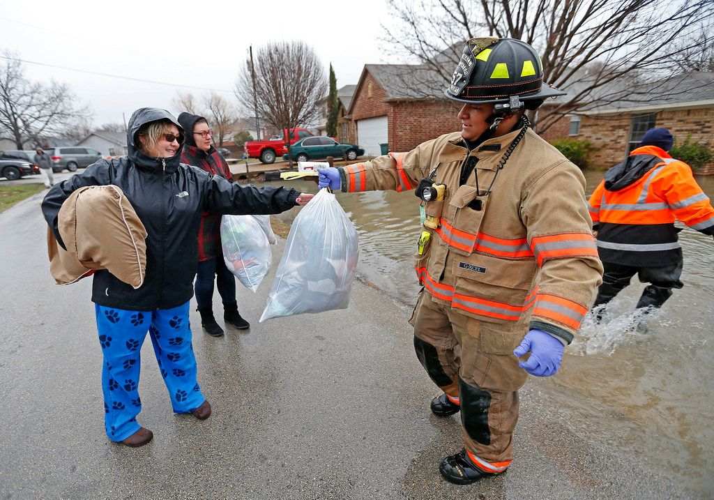 A Rockwall firefighter, right, gives a bag of clothing to Karen Sommers, whose friend lives in the house on Lakeside Drive in Rockwall, Texas, Thursday, Feb. 22, 2018.