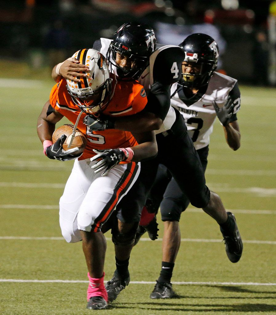 Haltom's Kenneth Cormier Jr. (5) is tackled by Euless Trinity's John Shead (4) after a first down run, during the second half of their high school football game on Oct. 11, 2019 in North Richland Hills. Haltom defeated Trinity 23-20. (Michael Ainsworth/Special Contributor)