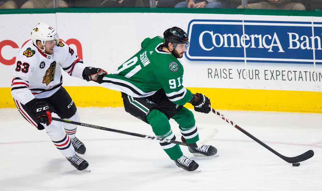 Dallas Stars center Tyler Seguin (91) has his jersey pulled by Chicago Blackhawks defenseman Carl Dahlstrom (63) during the first period of an NHL game between the Dallas Stars and the Chicago Blackhawks on Thursday, December 20, 2018 at American Airlines Center in Dallas. (Ashley Landis/The Dallas Morning News)