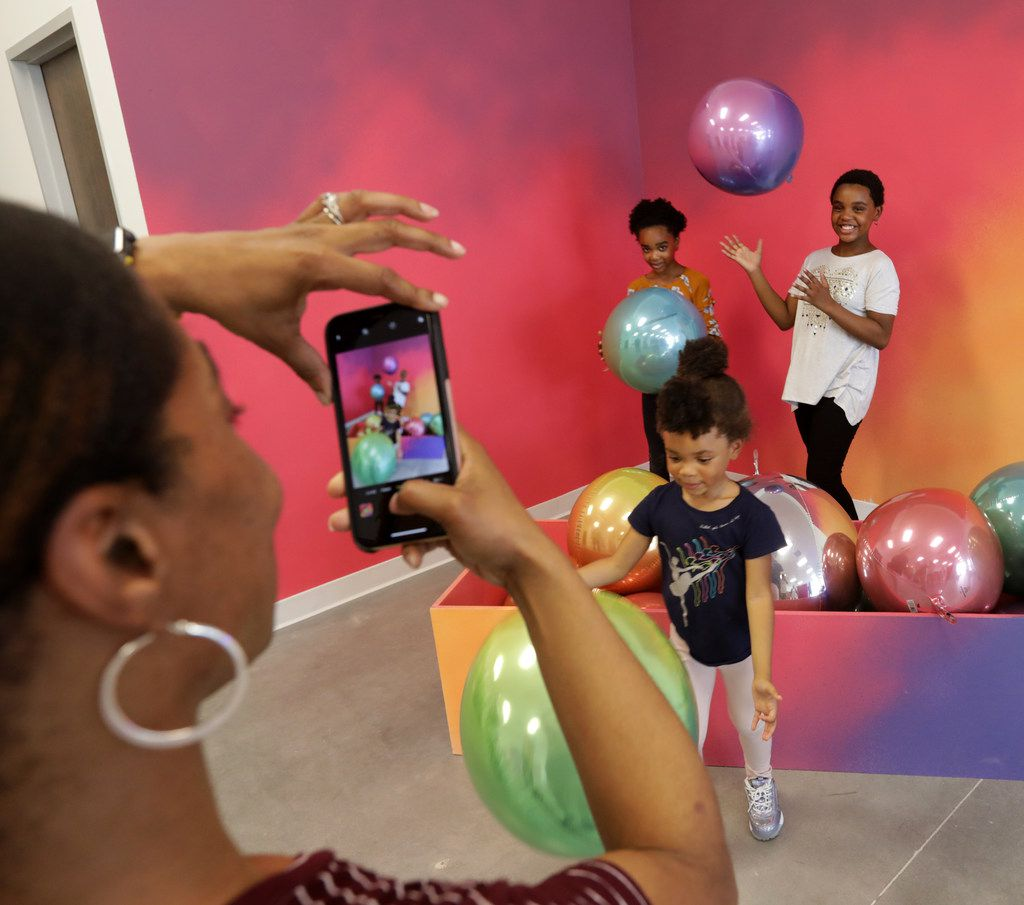 Philicia Carter-Blue, left, takes a photograph of 10-year-old J'Avia Carter-Blue, 4-year-old Dionna Carter-Blue, and 11-year-old Ja'Nihya Carter-Blue at the Snap151 pop-up photo studio in Frisco, TX, on Sep. 25, 2019. (Jason Janik/Special Contributor)