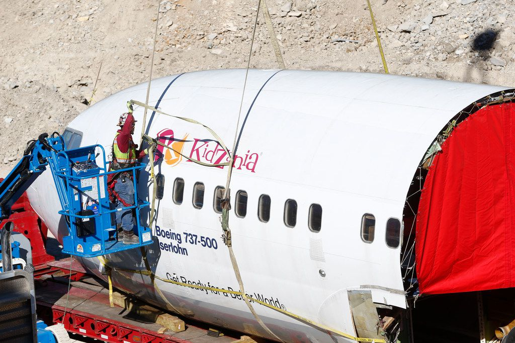 A construction worker secures the cockpit and front section of an airplane before moving it to what will be the entrance to KidZania at Stonebriar Centre mall in Frisco, Texas on Dec. 13, 2017.