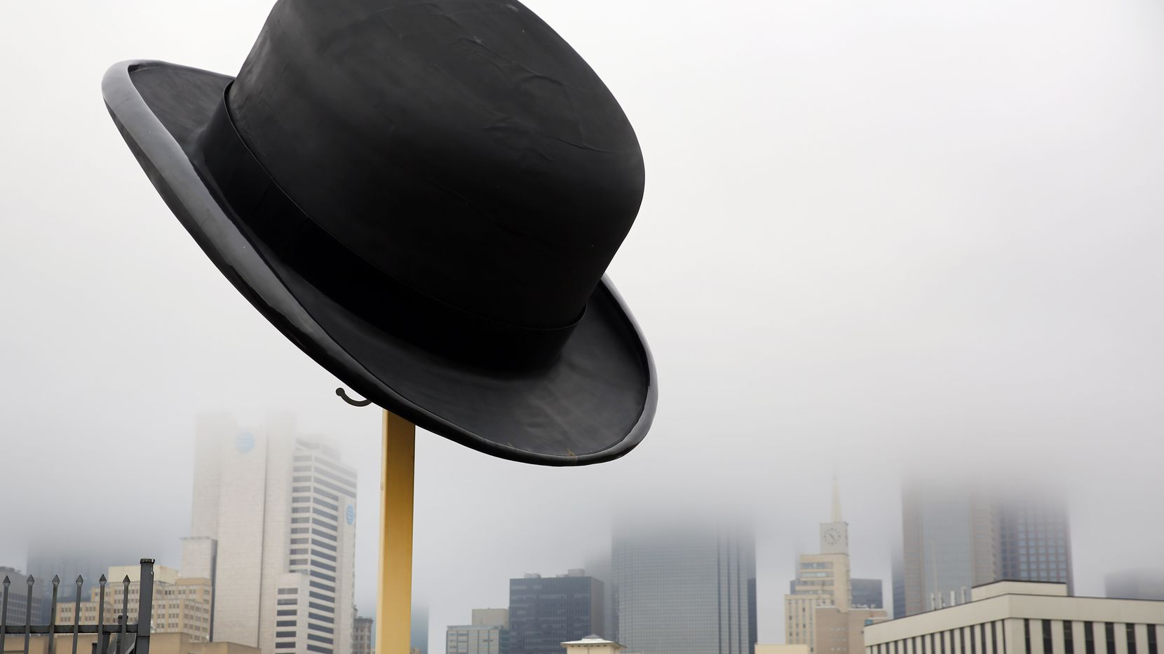 Downtown Dallas was shrouded by fog around a giant bowler hat sculpture by Keith Turman on Friday morning. Turman also created the 42-foot-tall, rolled-up umbrella in the Cedars neighborhood down the street on Akard. The National Weather service predicts more fog and drizzle Saturday and Sunday morning.