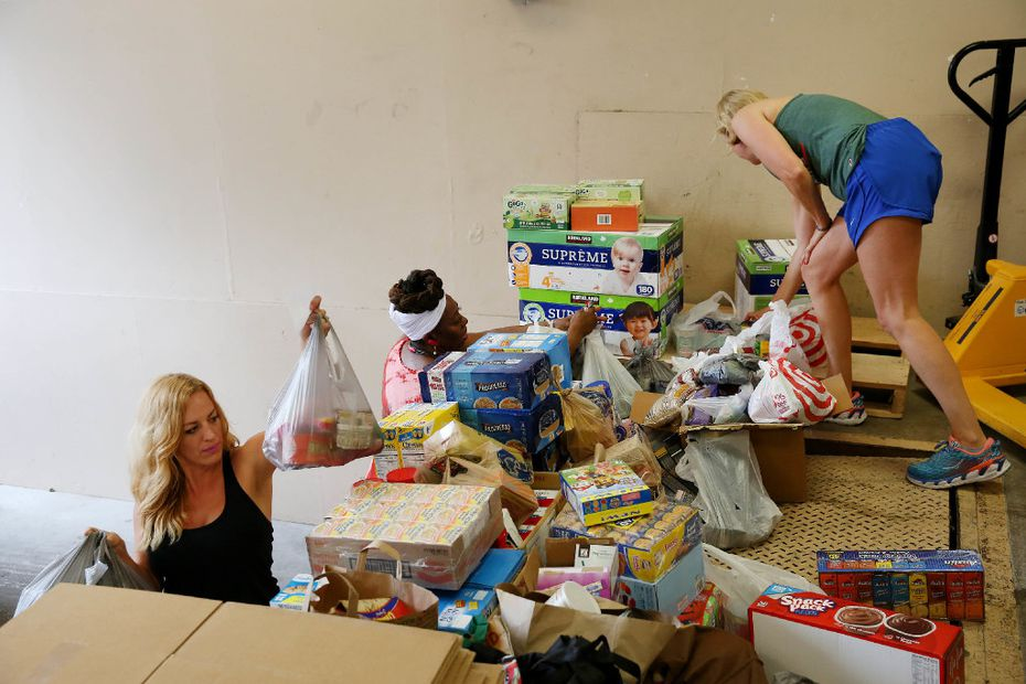 Taylor Grey (left) of Trusted World, Betty Reynolds (center) of Christian Chapel Temple of Faith and volunteer Rebecca Wilson organize donations at a drop-off location for Hurricane Harvey relief in Dallas.
