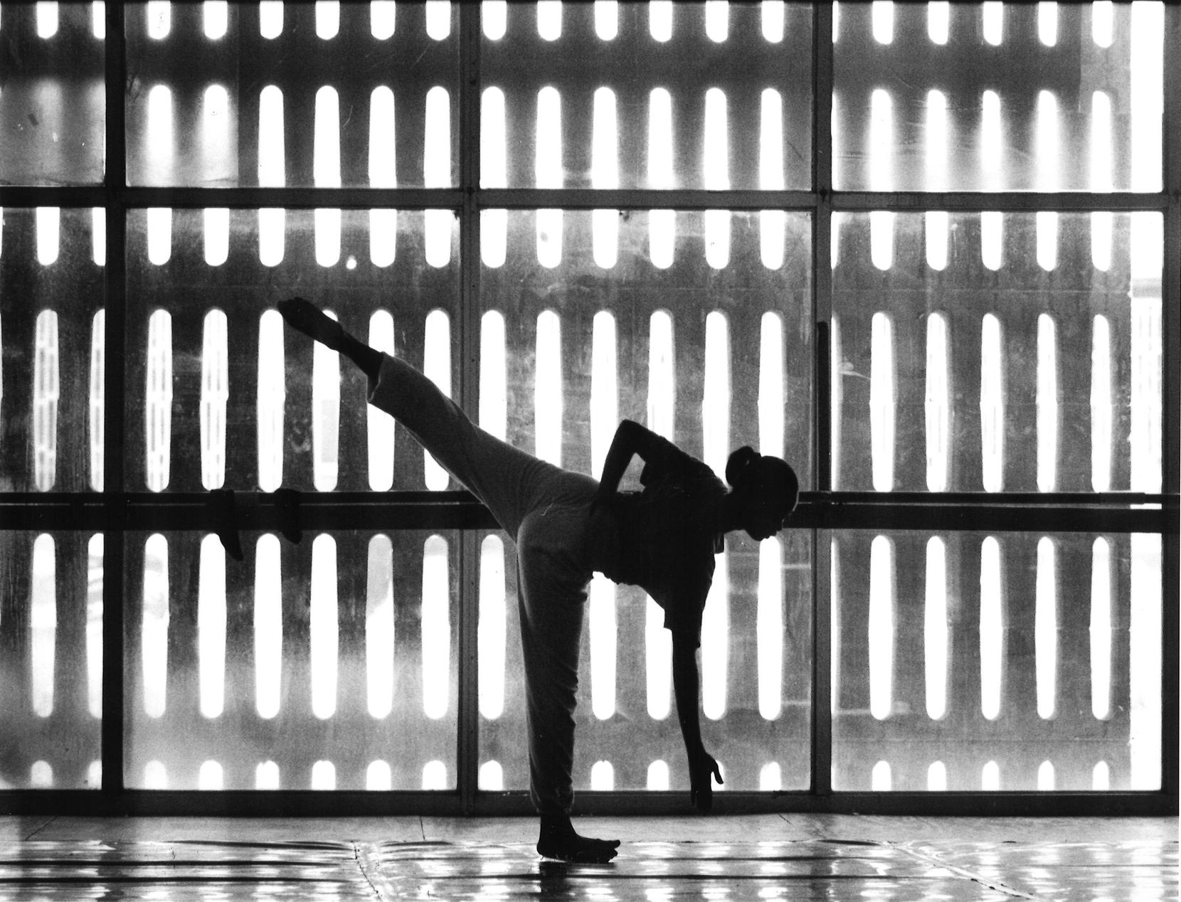 A dancer with the Dallas Black Dance Theatre stretching out before a rehearsal session in their Bishop College studio in 1988.