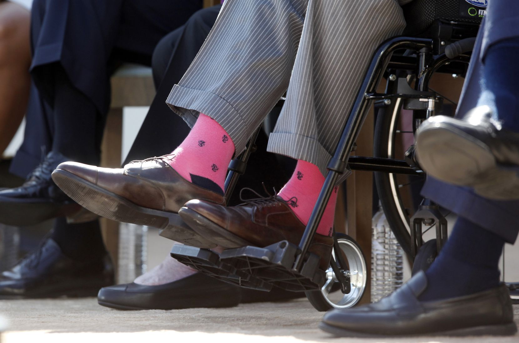 """2013: Former President George H.W. Bush wears pink socks as he is seated in a wheelchair at the dedication of the George W. Bush Presidential Library on the campus of SMU. In recent years the former president became known for wearing """"exuberant socks"""" in public."""