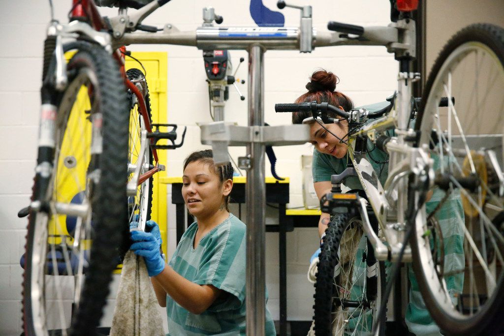 Patricia Greer (left) and Rosario Cervantes clean wheels during a bicycle maintenance class at Lew Sterrett Justice Center in Dallas.