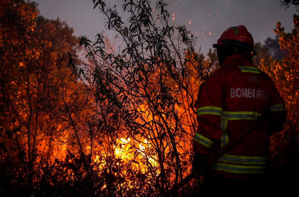 A firefighter combats a wildfire close to Monchique in the Portuguese Algarve, on August 8, 2018. - Wildfires scorched across Portugal's southern Algarve region today, threatening more villages as the country's prime minister warned the blaze could burn for days before being brought under control. Over 1,400 firefighters and soldiers were battling the blaze around the mountain spa town of Monchique in one of Europe's top tourist destinations.
