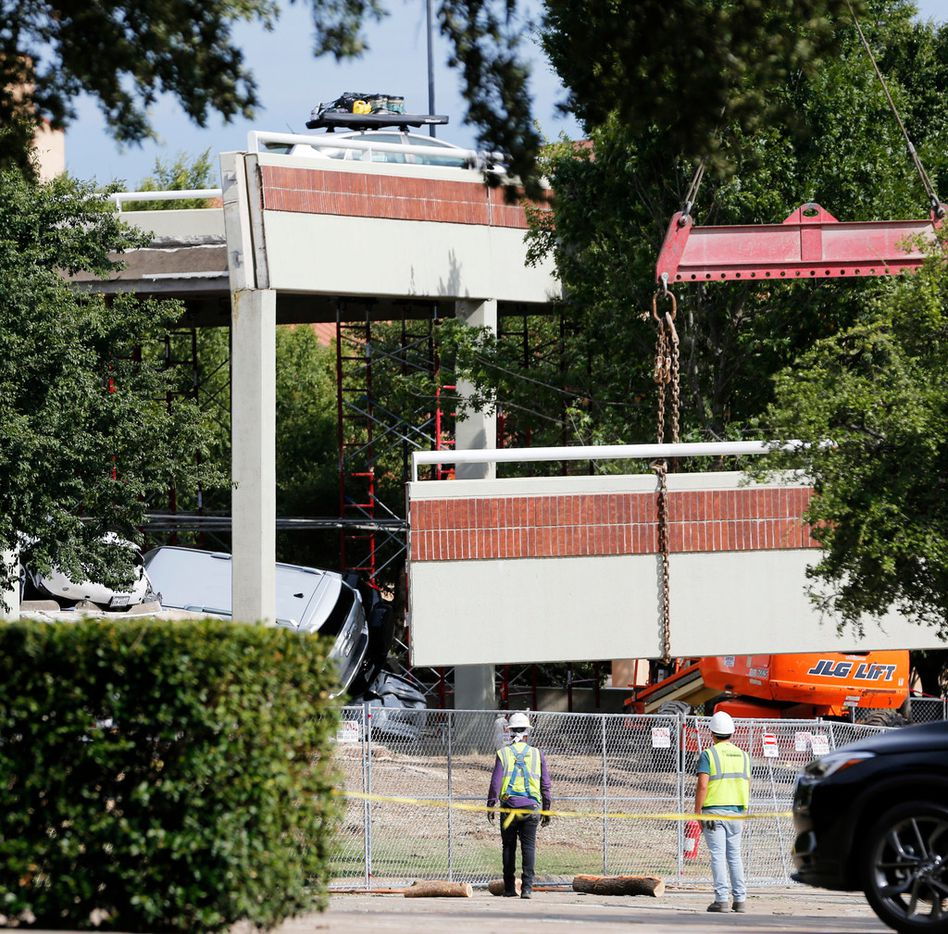 Workers are trying to remove six cars still trapped in the collapsed parking garage. (Vernon Bryant/The Dallas Morning News)