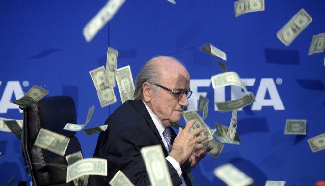 El presidente de la FIFA, Sepp Blatter, justo en el momento en el que un comediante británico, Simon Brodkin, le lanza billetes falsos. Blatter anunció que el nuevo mandamás de la FIFA será elegido en febrero. (AP/ENNIO LEANZA)