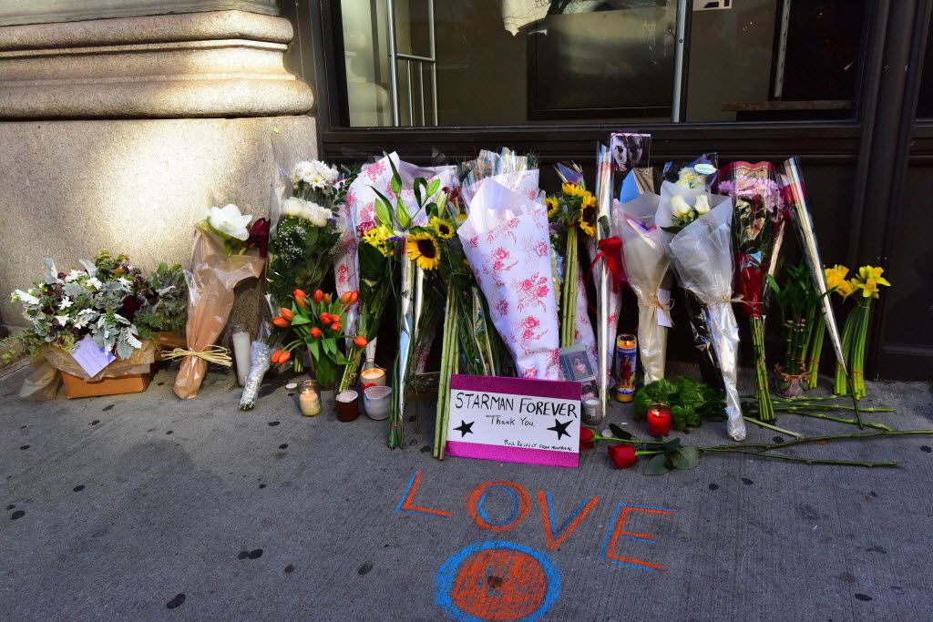 """Flowers and messages left outside the residence of British music legend David Bowie, on January 11, 2016, in New York. Bowie has died at the age of 69 after a battle with cancer, drawing an outpouring of tributes for one of the most influential and innovative artists of all time. A notoriously private person, Bowie's death came as a shock for the world just days after he had released his 25th studio album """"Blackstar"""" on his 69th birthday on January 8. """"David Bowie died peacefully today (Sunday) surrounded by his family after a courageous 18 month battle with cancer,"""" said a statement posted on his official social media accounts on January 11."""