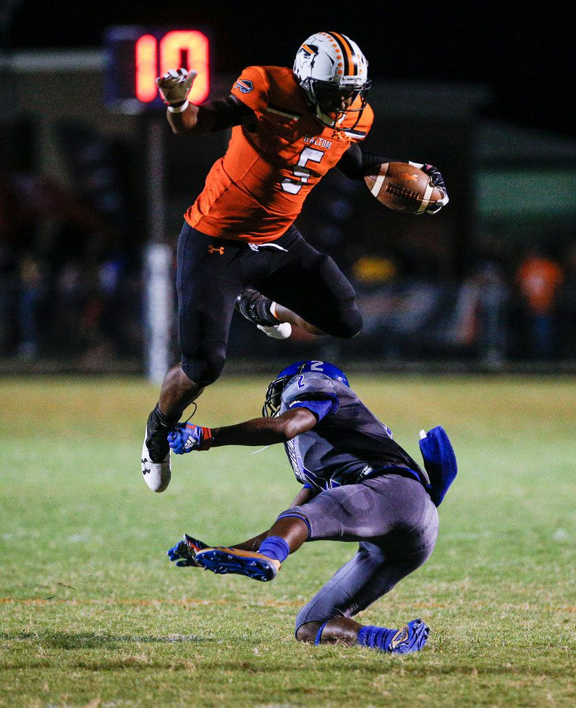 TXHSFB Haltom City senior running back Kenneth Cormier Jr. (5) jumps over North Mesquite senior defensive back Torrion Smith (2) during the first half of a high school football game at Birdville Stadium in Haltom City, Friday, September 20, 2019. (Brandon Wade/Special Contributor)