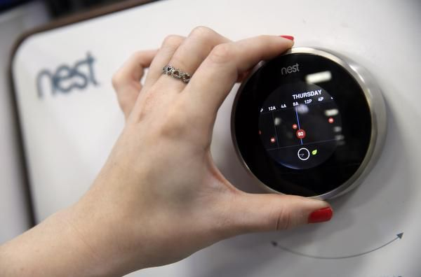 A Best Buy sales associate shows how to adjust a smart thermostat from Nest. Electricity providers are promoting the thermostats as a way for consumers to control costs and as a way for the companies to prevent blackouts.