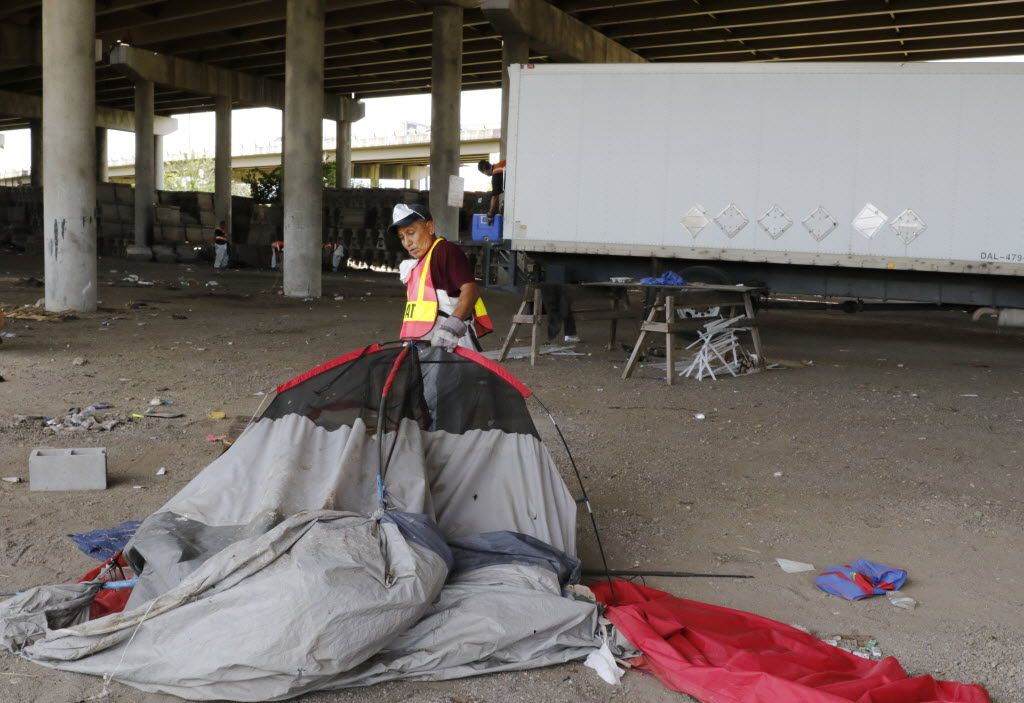Agustin Alvarado picks up trash at a homeless encampment at Coombs Street under Interstate 45. The shantytown was the second closed in Dallas this year. (File Photo/David Woo)