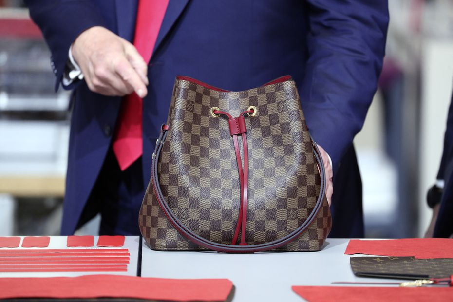 President Donald Trump looks at a bag during his visit to the new Louis Vuitton workshop.
