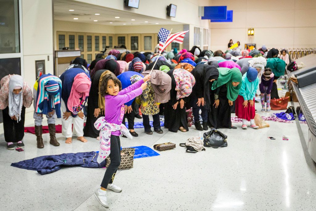 A young girl waves the American flag as Muslim women set down their protest signs to pray at DFW International Airport where they gathered in opposition to President Donald Trump's executive order barring certain travelers on Sunday, Jan. 29, 2017.