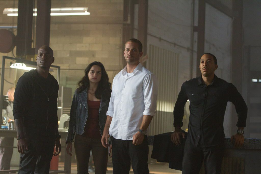 """This photo provided by Universal Pictures shows, from left, Tyrese Gibson as Roman, Michelle Rodriguez as Letty, Paul Walker as Brian, and Chris Ludacris as Tej, in a scene from """"Furious 7."""""""