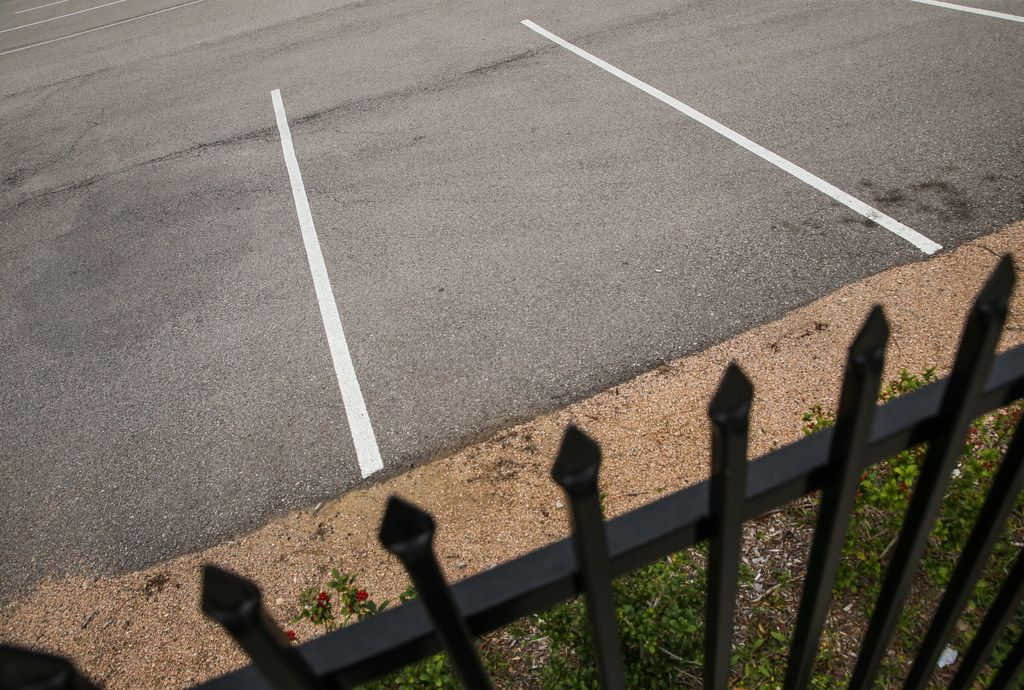 A locked fence and empty parking lot is seen Feb. 6, 2019, in the 2200 block of Burbank Street in Dallas.