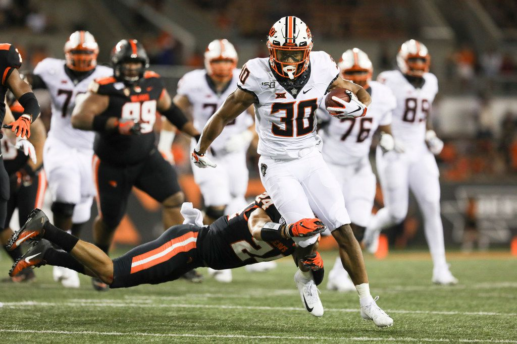 Oklahoma State wide receiver Gabe Simpson (30) is brought down by Oregon State defensive back David Morris (24) during the first half of an NCAA college football game in Corvallis, Ore., Friday, Aug. 30, 2019. (AP Photo/Amanda Loman)