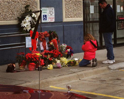 A girl and her father say a prayer for fallen Irving police officer, Aubrey Hawkins, in front of the Oshman's in 2000. Hawkins was killed outside the were he was killed during a Christmas Eve 2000 robbery by seven Texas prison escapees.  The Irving Citizens on Patrol were also there putting black ribbons on cars in memory of the officer.