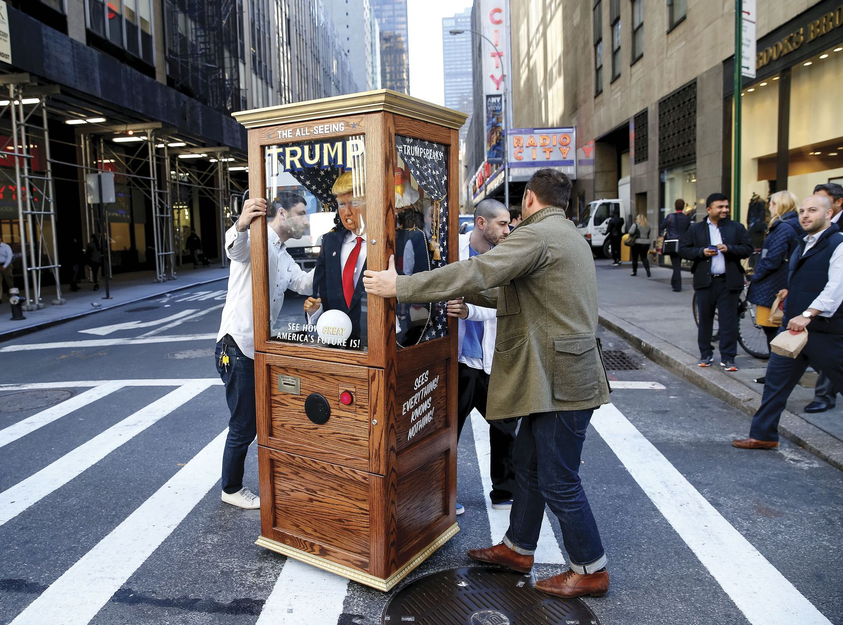 Artist Nathaniel Lawlor got some help from friend Jason Goodman as they pushed a fortune teller machine bearing Donald Trump'€™s image outside the Midtown Hilton in New York City on Nov. 8, 2016. When the red button is pushed, Trump's voice recites some of his famous and funny lines.