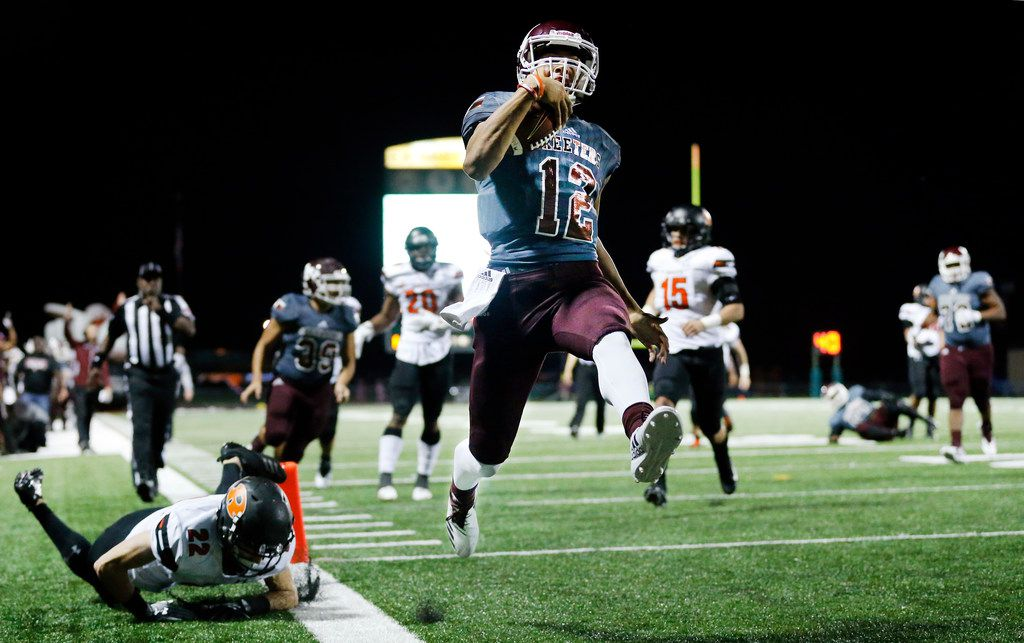 Mesquite quarterback Dylan McGill (12) skips through the end zone, scoring a second quarter touchdown against Rockwall defensive back Tyler Ainsworth at E.H. Hanby Stadium in Mesquite, Texas, Thursday, November 1, 2018. (Tom Fox/The Dallas Morning News)