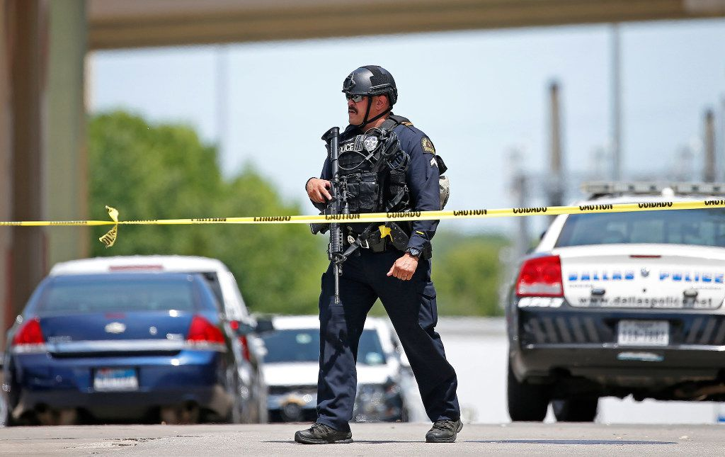 A Dallas Police Department officer leaves an shooting scene outside an office building in Lake Highlands near the High Five where police found two people dead inside the office building in Dallas, Monday, April 24, 2017. Crowe (Jae S. Lee/The Dallas Morning News)