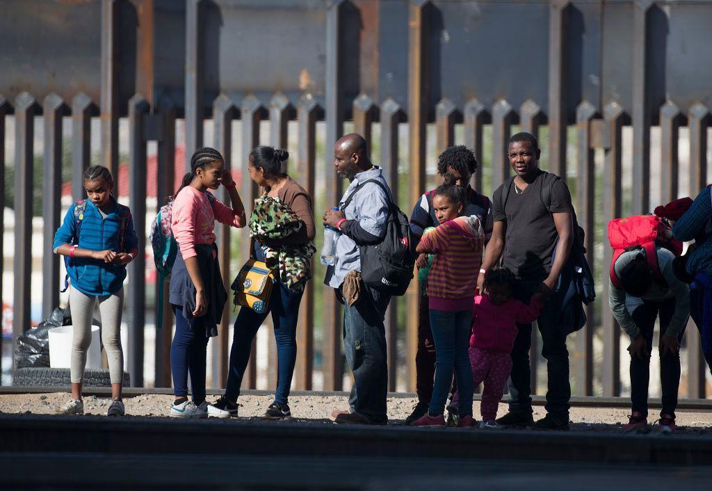 Un grupo de migrantes de Centroamérica espera junto a la barda fronteriza en El Paso, Texas, para ser procesados por autoridades migratorias. (Getty Images/Joe Raedle)