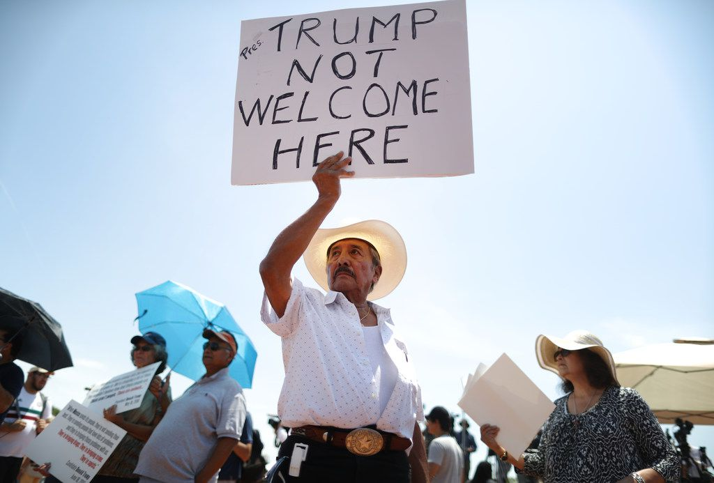 Miguel de Anda, born and raised in El Paso, holds a sign reading 'Trump Not Welcome Here' at a protest against Trump's visit to El Paso following the mass shooting there.