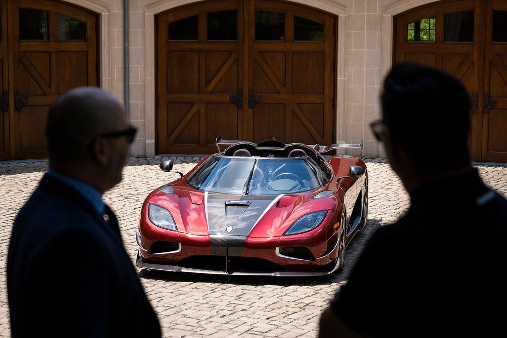 Visitors are silhouetted as they see the Koenigsegg Agera RS on display in the driveway of Ted Skokos' carriage house.