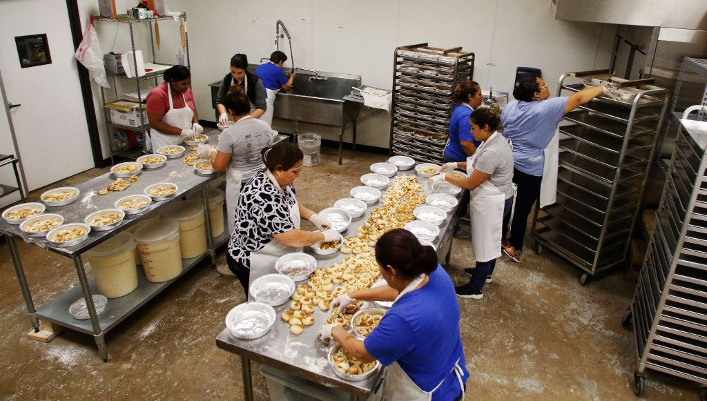 Lorena Garcia (center) and Eglantina Nunez (top in blue)  and others make freshly baked cinnamon rolls at RoRo's Baking Company in Dallas.