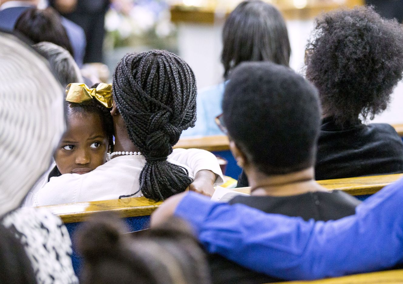 A young girl (far left) looks back at Allison Jean, (foreground center, back to camera) mother of Botham Shem Jean, during a prayer service for Botham Shem Jean at the Dallas West Church of Christ on Sunday, September 9, 2018 in Dallas.
