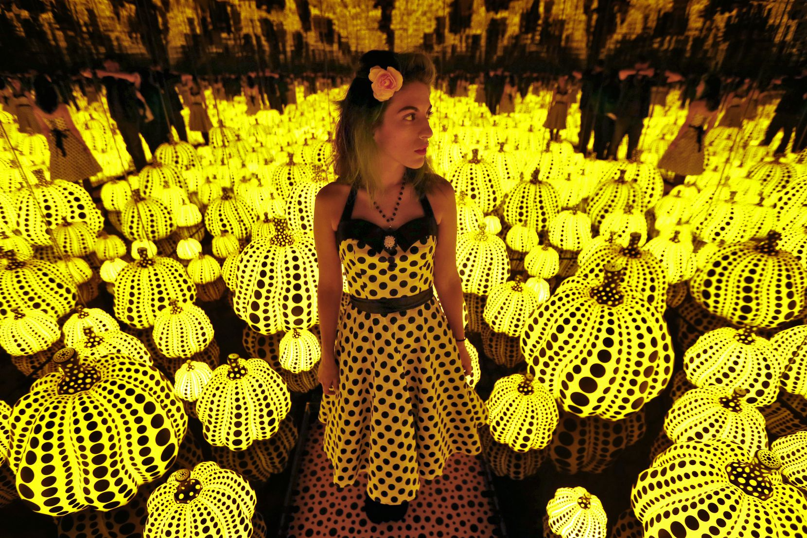 Lyza Hernandez looks at the Yayoi Kusama's installation: All the Eternal Love I Have for the Pumpkins, at the Dallas Museum of Art in Dallas on Sept. 22, 2017.