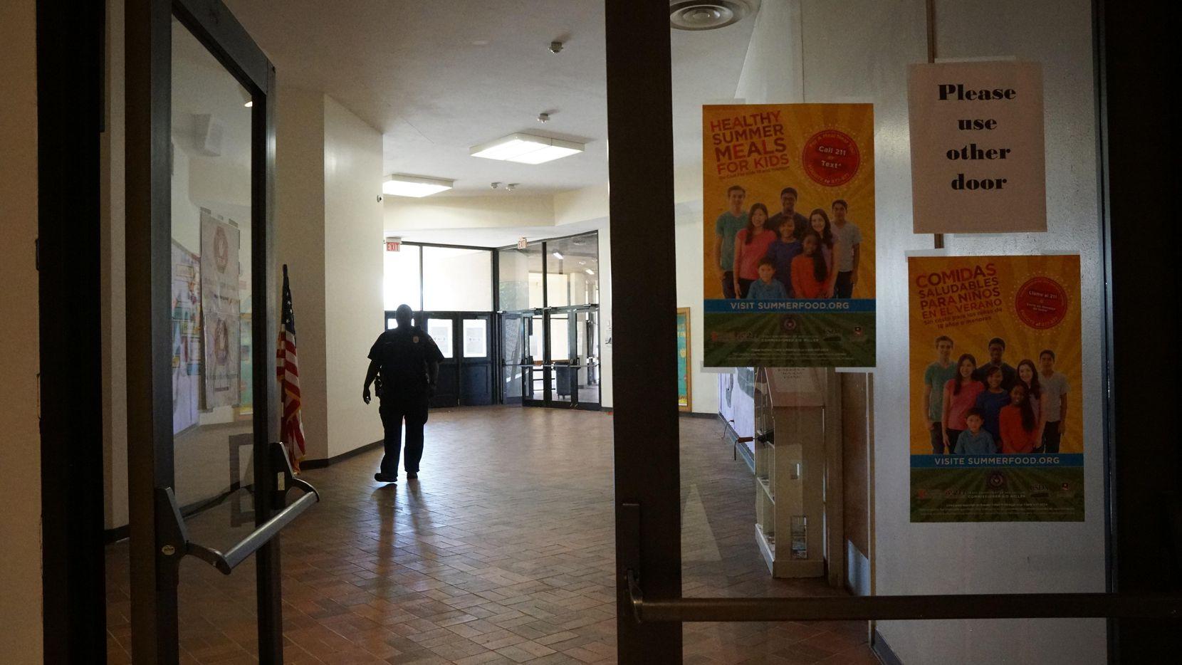 Un guradia de seguridad camina por los pasillos de Manns Education Center en Dallas.