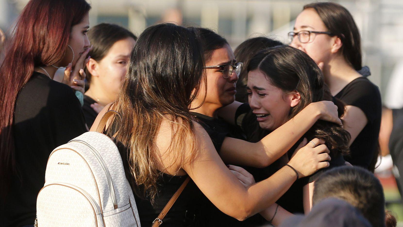 Familiares de Javier Amir Rodríguez se abrazan al inicio de un servicio memorial luego de la muerte del joven en Horizon High School en El Paso, Texas.