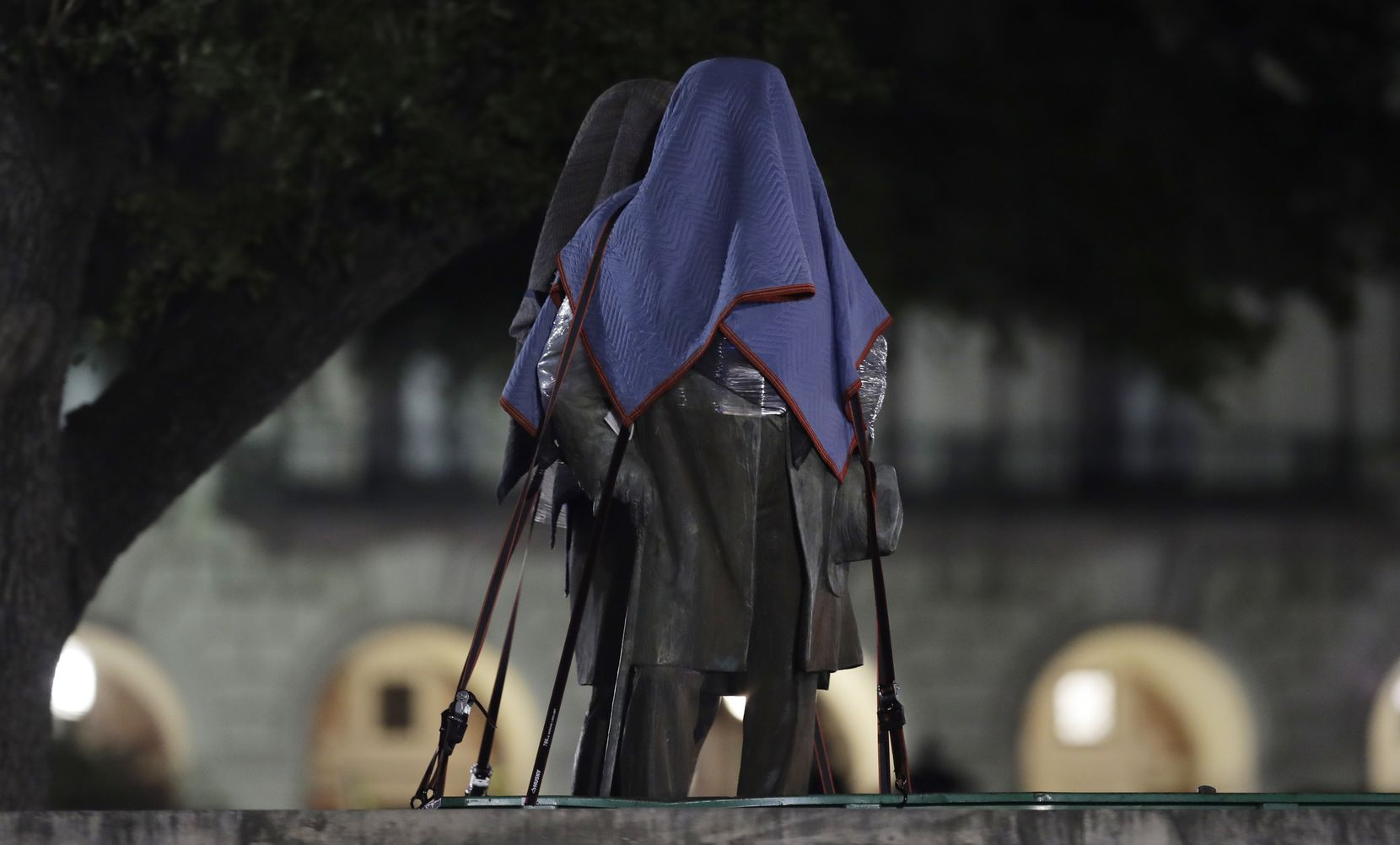 Confederate statutes removed from the University of Texas were covered and secured to a trailer early Monday morning in Austin.