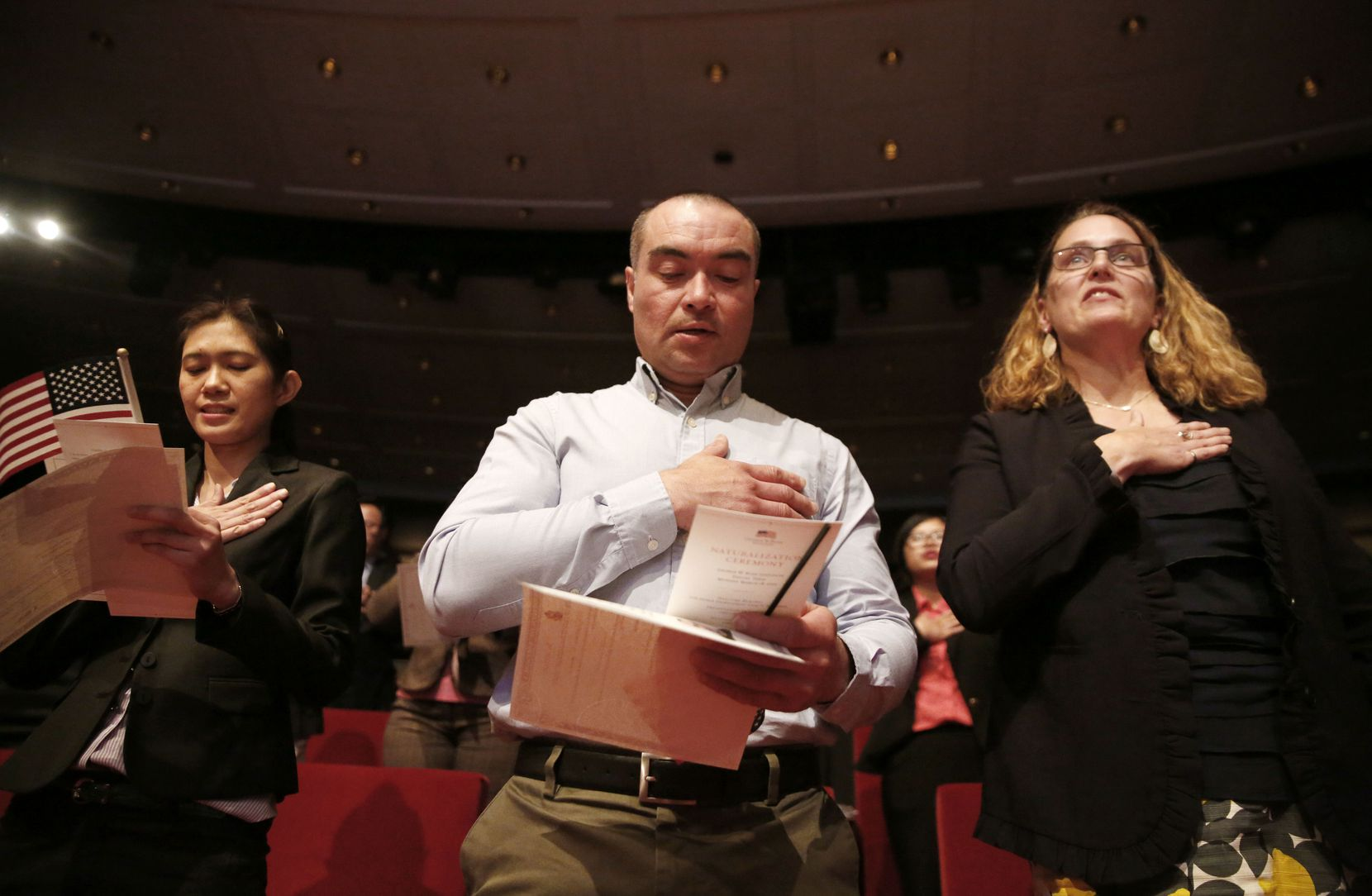 New U.S. citizens (from left) Supinya Phapant, of Thailand, Julio Martinez, of El Salvado,r and Mary McCarthy, of Canada, recite the Pledge of Allegiance during a naturalization ceremony at the George W. Bush Presidential Center in Dallas on Monday, March 18, 2019.
