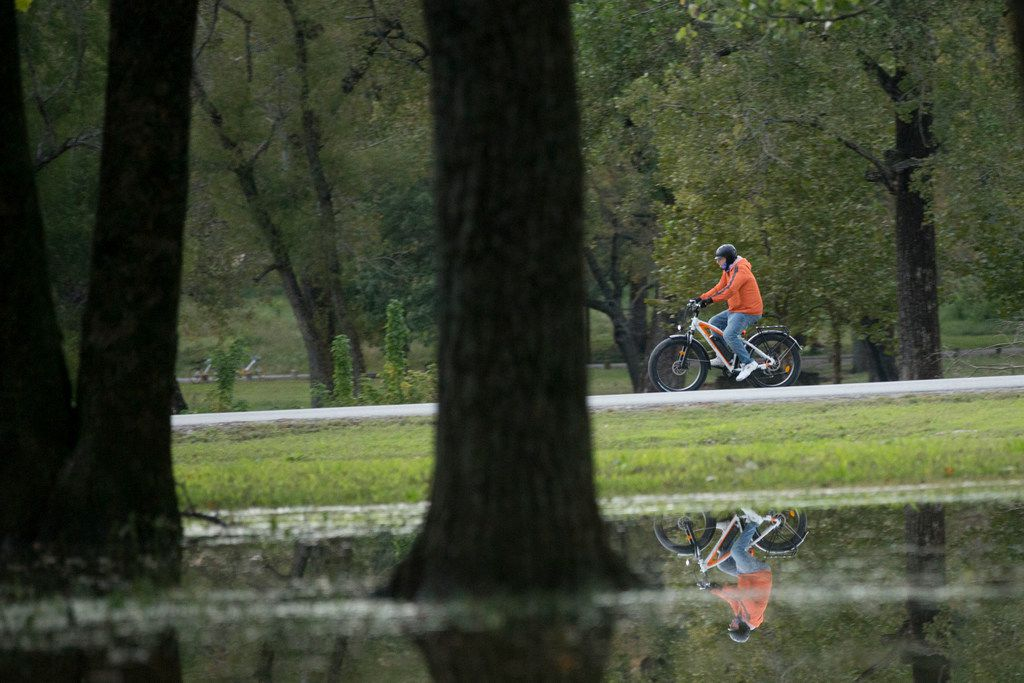 A cyclist is reflected in water left standing after recent heavy rains while riding along Lawther Drive near White Rock Lake in Dallas.